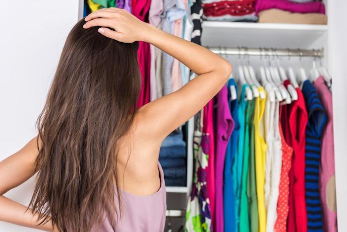 kleiderschrank mit vielen bunten klamotten und eine frau mit langem haar