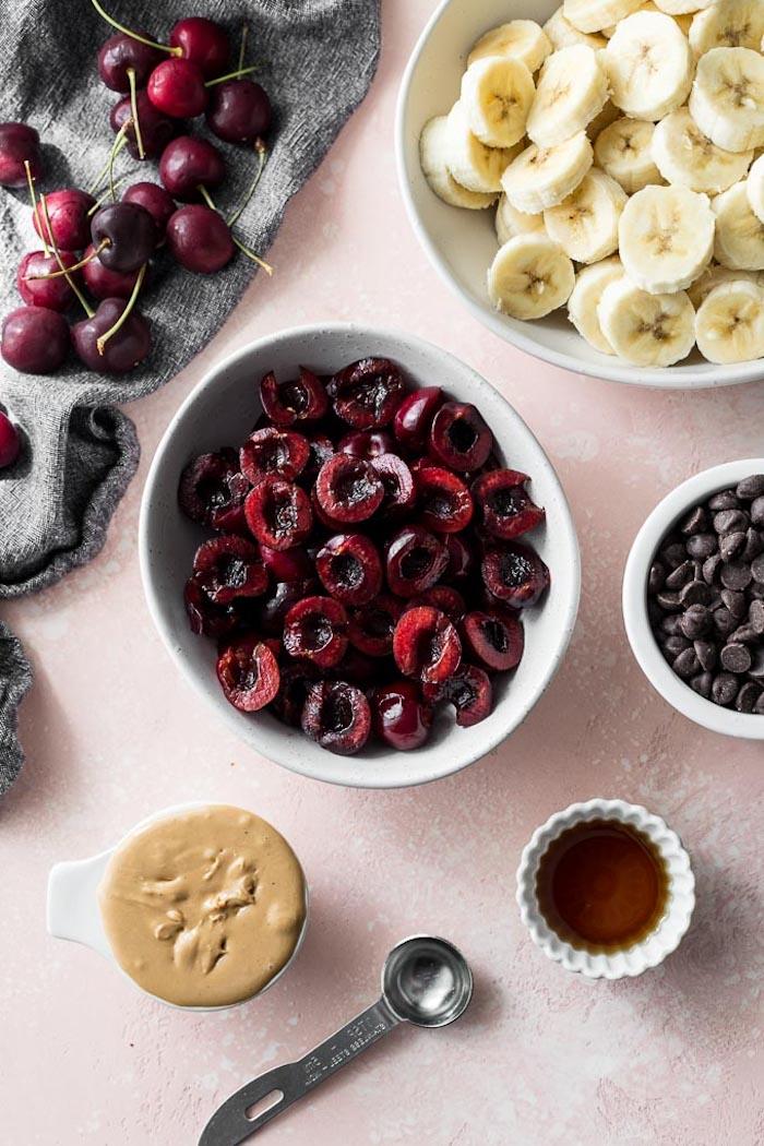 Zutaten für selbstgemachtes Eis, halbierte Kirschen, Bananenscheiben Erdnussbutter Honig und Schokoladenstücke