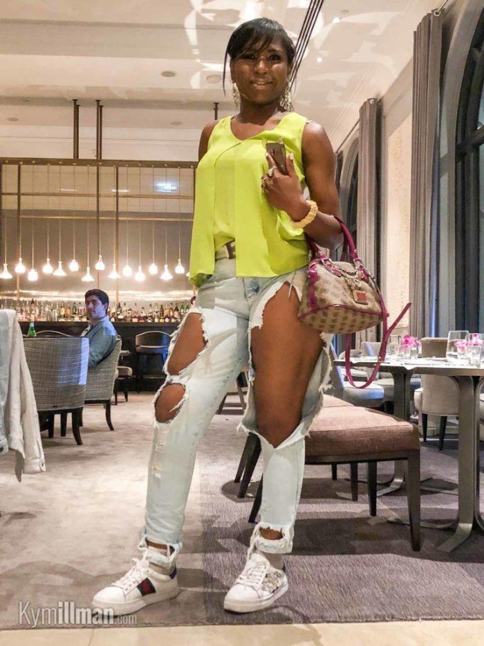 alternative kleidung, eine schöne junge frau mit gelbem top, gerissene jeans, weiße sneakers, die kleidung austragen