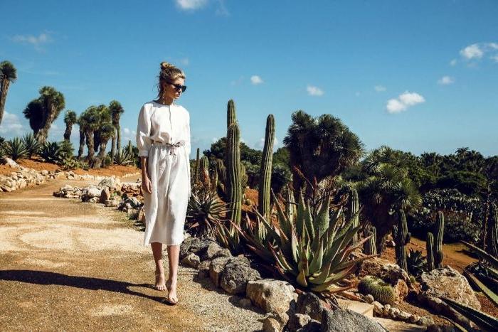 bio kleidung, eine junge schöne dame in der wüste mit kaktus pflanzen rund herum, weißes outfit