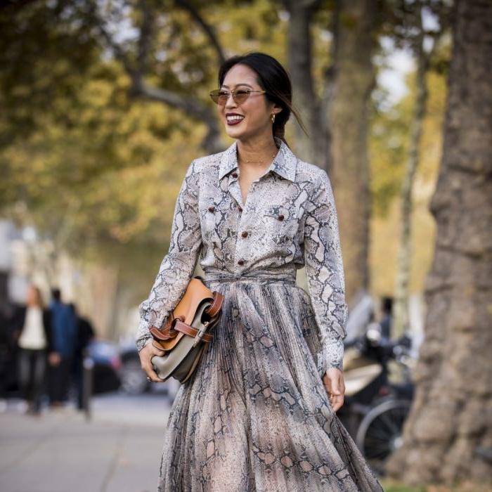 fair trade kleidung, eine schöne frau mit schlangen outfit, rock und hemd mit einer tasche in neutralen farben, coole brille