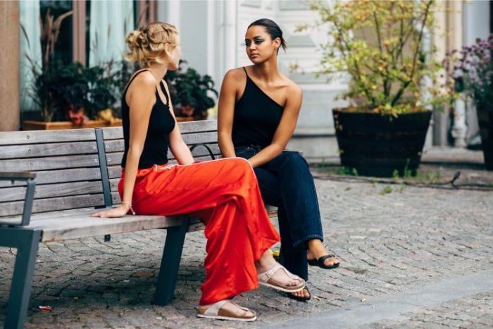 schwedische mode für damen, zwei freundinnen sitzen auf einer bank und sprechen, rote hose, dunkler jumpsuit