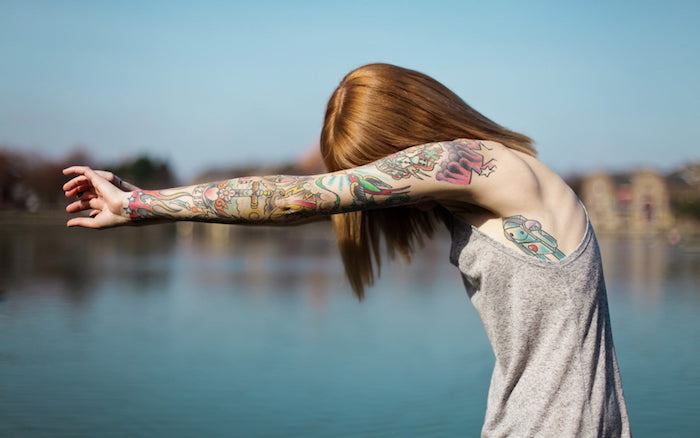 Farbige Tattoos am ganzen Arm, graues Top, kupferrote Haare mit Pony, See im Hintergrund