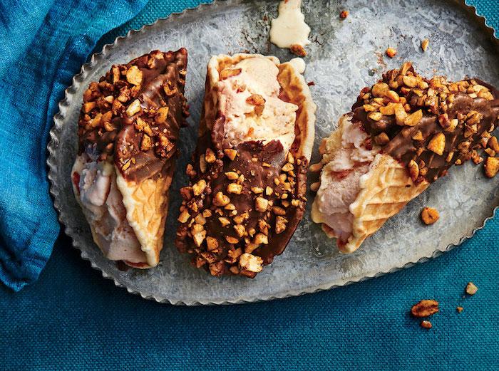 Süße Tacos Idee, Waffeln gefüllt mit Schokoladeneis, getunkt in Schokolade mit Nüssen