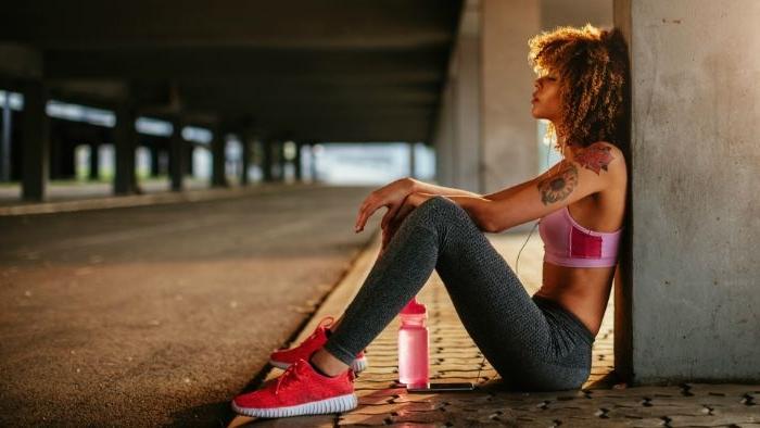 dänische kondermode und mode für teenager und sportler, eine frau mit sportlichem bra und jeggings sitzt auf dem boden, rosa trinkflasche für sport