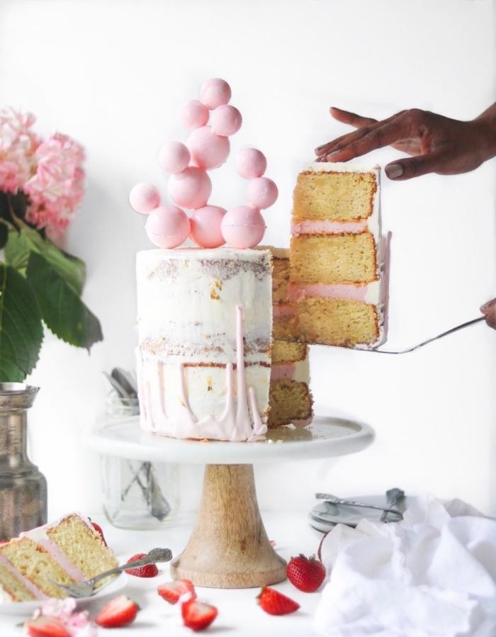 geburtstagsluchen mädchen, torte mit erdbeeren dekoriert mit sahne und bällchen aus rosa schokolade