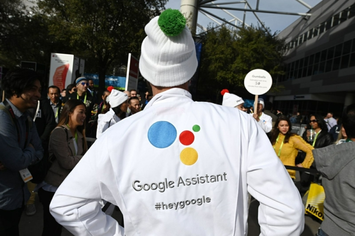 Google Assistant liest, ein Mann, der sich als Google Assistant verkleidet hat