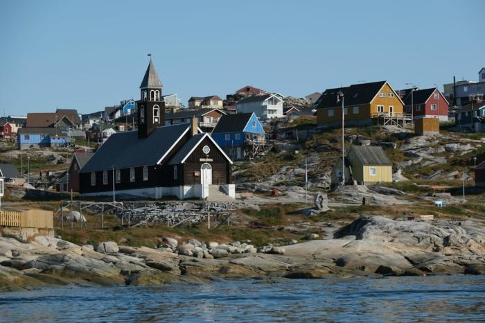 blauer Himmel, kleine Häuser in Grünland an der Meeresküste, sehr schöne Aussicht