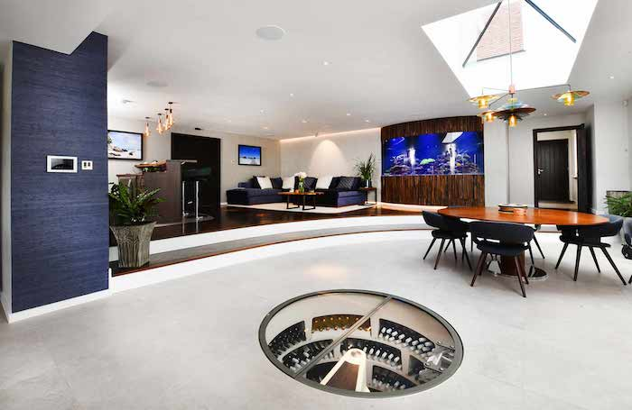 Luxuriöses Wohnzimmer, großer runder Tisch, gemütliche Ecke für Relaxen, Weiß mit Holzelementen