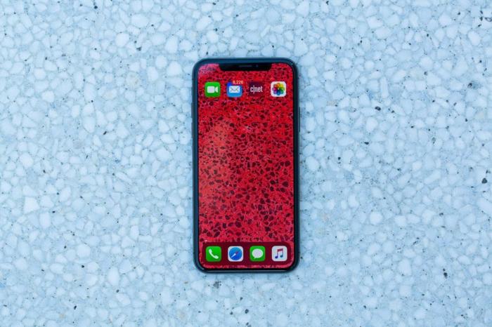 iPhone 11, ein rotes Smartphone in dem Badezimmer, es fotografiert die Fliesen