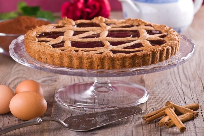 linzer torte rezept, ein kuchen auf eine glasplatte spezielle stelle für kuchen und torte, eier und zimt deko darum