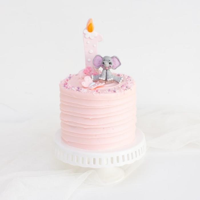kuchen zum 1 geburtstag, torte für mädchen, geburtstagstorte dekoriert mit rosa creme und kleiner figur, elefant