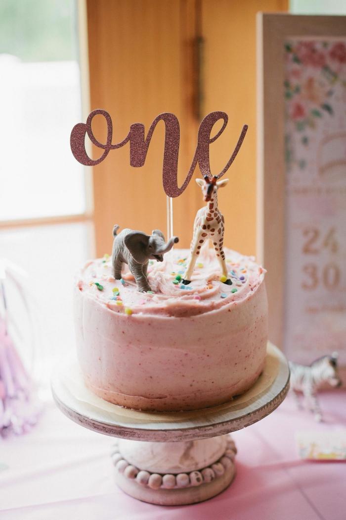 torte dekoriert mit rosa kreme und zwei figuren, kuchen zum 1 geburtstag, giraffe, elefant
