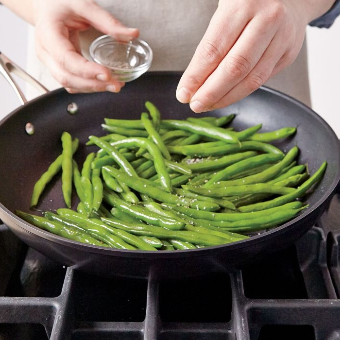 schnelle rezepte mittagessen, erbsen, grünes frisches gemüse in der pfanne mit salz und pfeffer würzen
