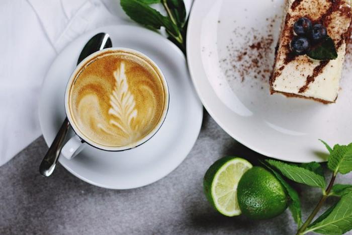 linzertorte, kaffee it kuchen und limetten als deko daneben, eine tassee mit cappuccino