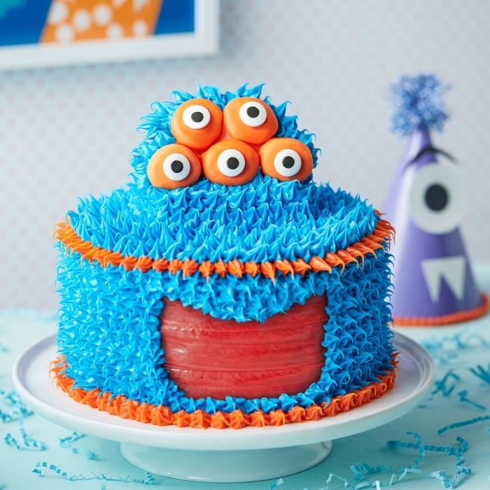 lustige kuchen kindergeburtstag, geburtstagstorte ungeheuer dekoriert mit blauer und orangenfarbener buttercreme, fünf augen