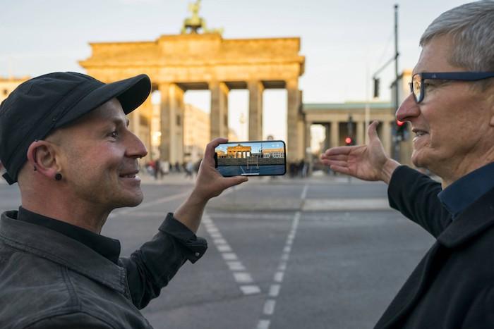 brandenburger tor in berlin, zwei männer und ein smartphone mit der app mauAR, die die ehemalige berliner mauer zeigt