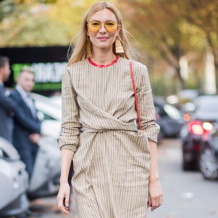 bio mode, eine schöne blonde frau mit gelben sonnenbrillen, ein kleid, rote tasche, große ohrringe