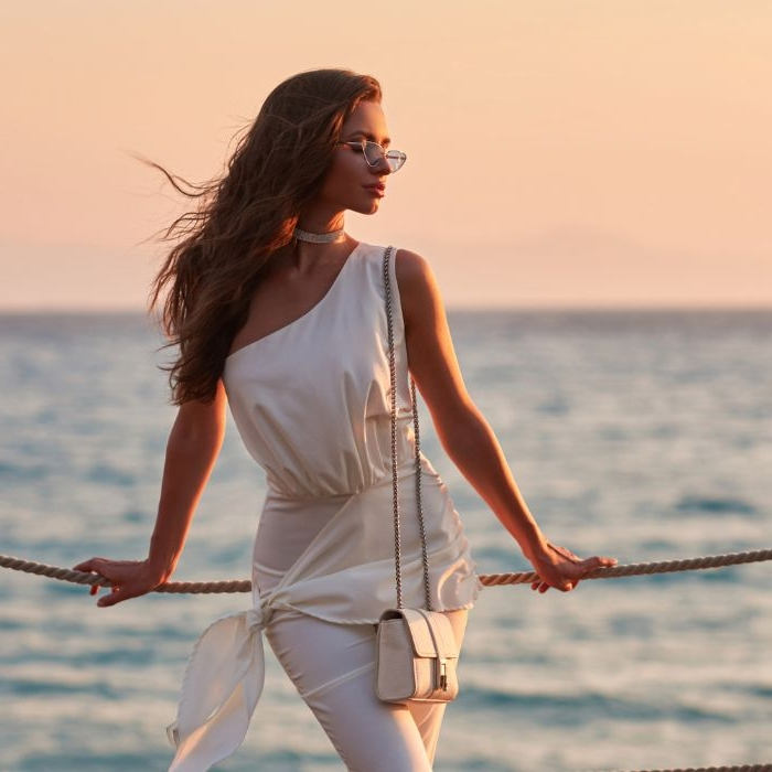 nachhaltige kleidung für frauen, weiße kleidung top und hose, eine weiße kleine tasche, sonnenbrille, foto beim sonnenuntergang