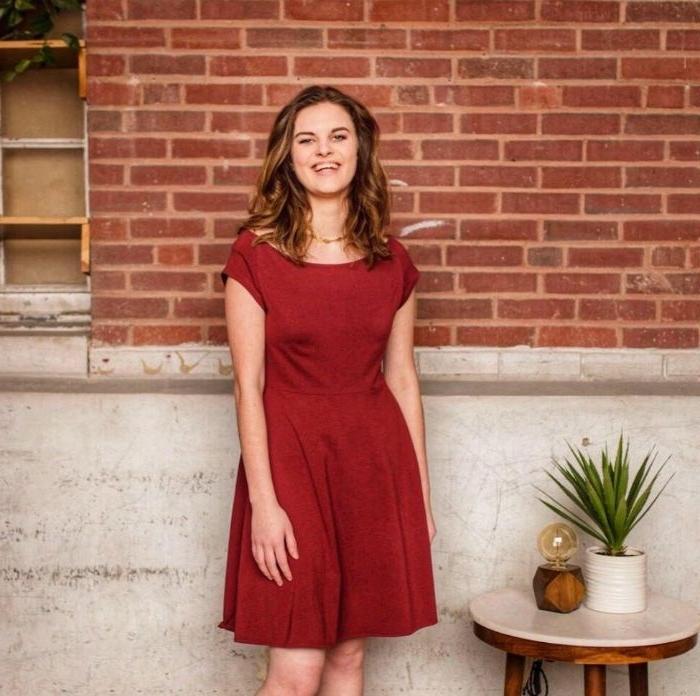 nachhaltige kleidung, rotes kleid mit kurzen ärmeln, eine pflanze auf kleinen kaffeetisch