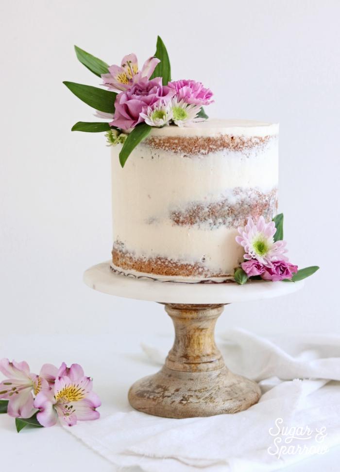 kleine torte dekoriert mit weißer creme, naked cake hochzeitstorte, rosa blüten