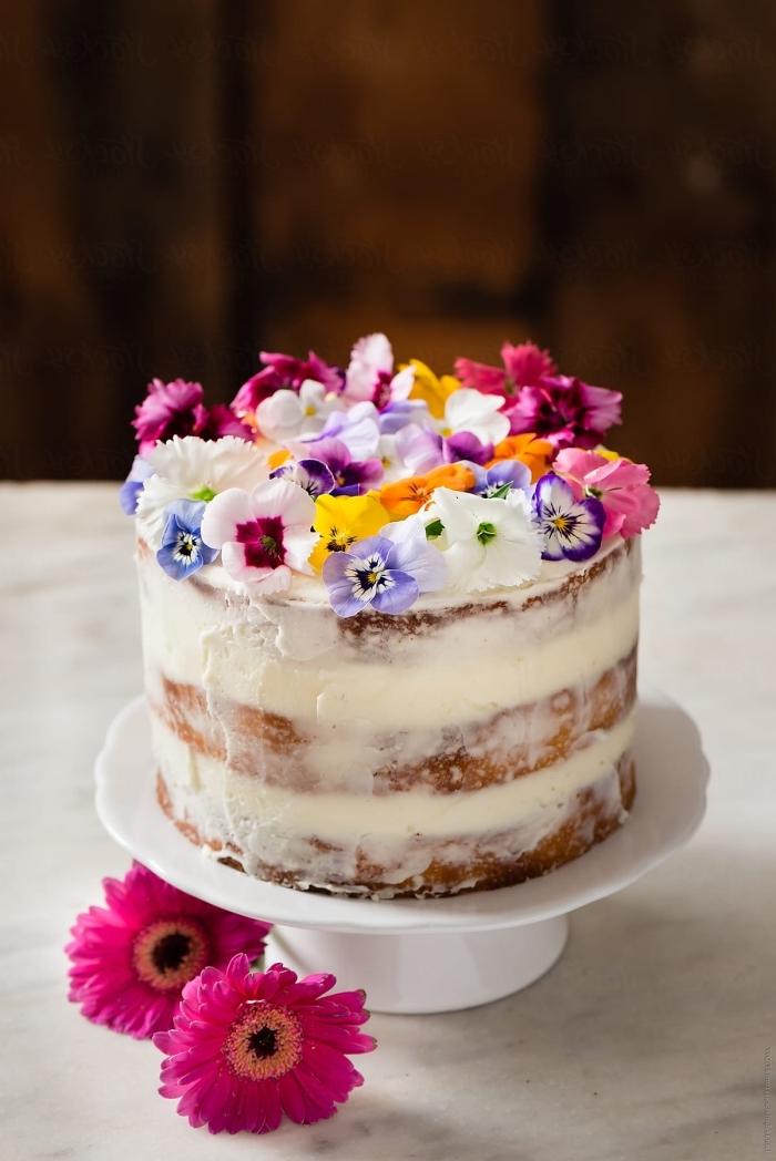naked cake mit vanille und weiße sahne dekoriert mit kleinen bunten blüten, sommer party essen