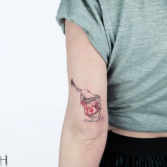 Lustiges Tattoo am Oberarm, Maus mit Blasinstrument und Bluse mit Herzen