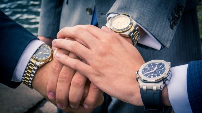 drei elegante Herren, jeder hat seine eigene Luxusuhr und nur die Hände sind zu sehen