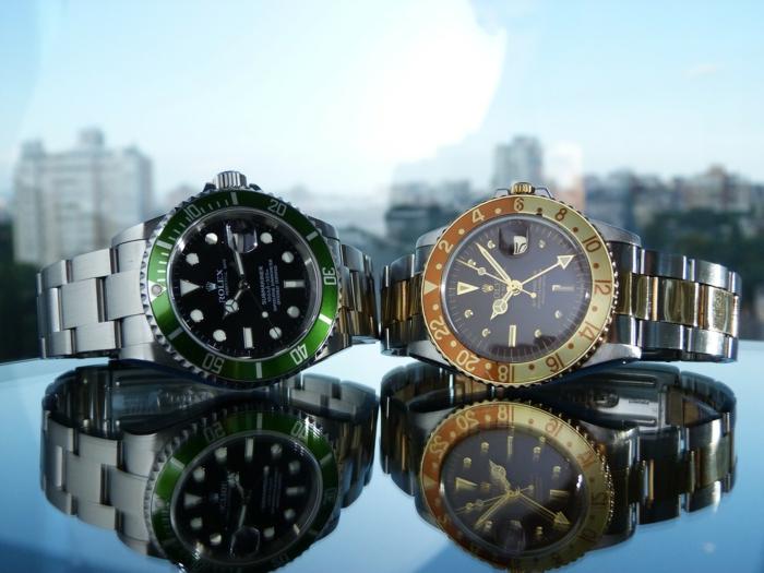 zwei Uhren in grünen und gelben Farben, die Oberfläche widerspiegelt die Uhren, Luxusuhren
