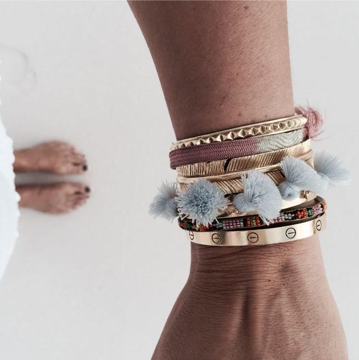 skandinavische mode marken, viele armbänder am arm, cartier modell, goldene, flauschige motive u.a