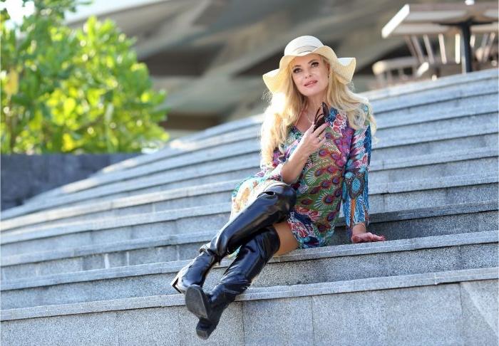 skandinavische mode marken, eine frau mit blonden haaren und einen hut, buntes kleid in neutralen tönen und hohe stiefel