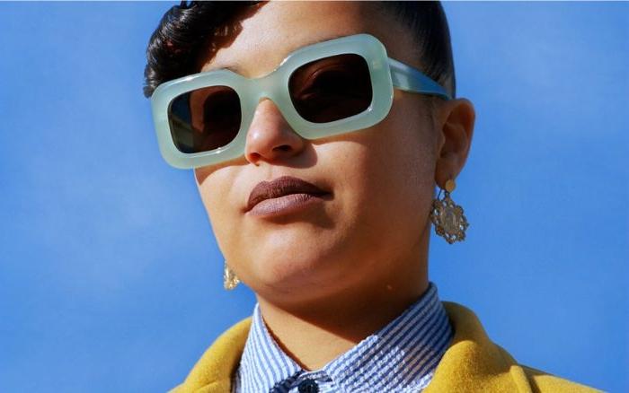 ökologische kleidung, eine frau mit grünen quadratischen brillen, gelbe jacke, blaues hemd