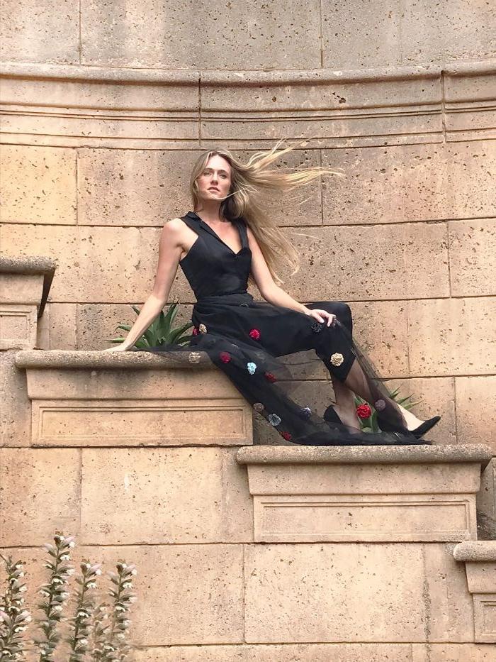 nachhaltige produkte, eine junge frau mit blonden haaren, schwarzes outfit, blumenprint