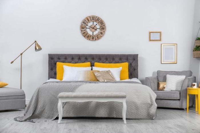 schöne schlafzimmer, graues bett, gelbe kissen, wanduhr dekoration, lampe, bilder deko