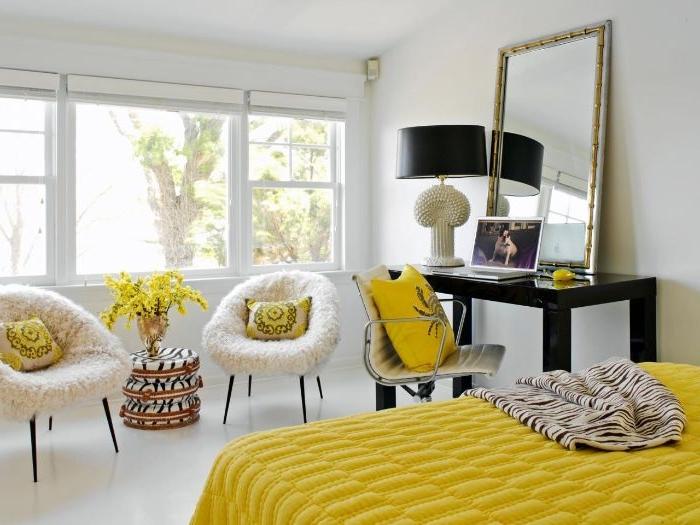 schöne schlafzimmer, gelbes bett, zwei sessel mit kissen, ein großes spiegel auf dem kleinen schreibtisch, lampe schwarz und weiß