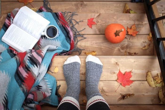 skandinavische mode marken, graue socken, weiße details deko ideen, kürbis, kaffee, buch auf einer bunten decke