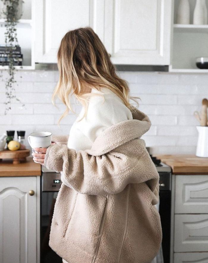 skandinavische mode marken, flauschige mantel idee, weißes tshirt, eine frau in der küche
