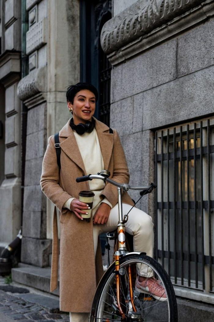 kataloge damenmode, eine junge und stilvolle frau mit fahrrad und weißen outfit und beigem mantel