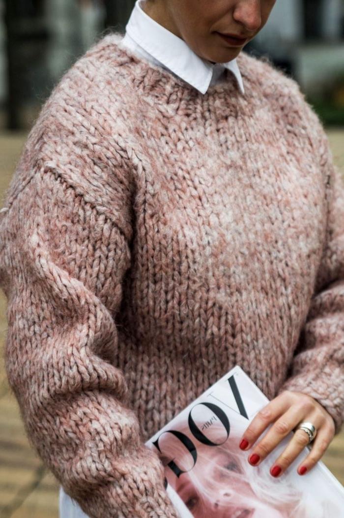 schwedischer onlineshop mode, eine frau mit sehr dickem rosaroten pullover, ein magazin in der hand und ring, hemd unter dem pulli