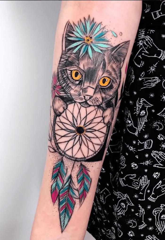 Auffälliges Tattoo am Unterarm, Katze mit blauer Blume, Traumfänger mit lila blauen Federn