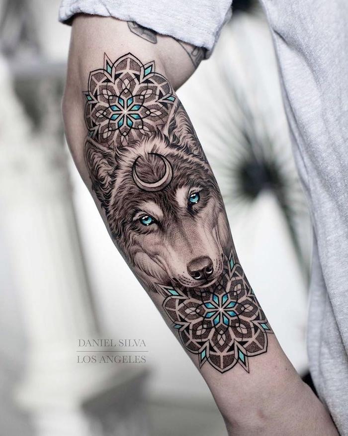 Wolf Tattoo am Unterarm, Wolf mit Halbmond am Stirn und blauen Augen, zwei Mandala Blumen
