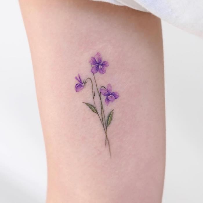 Zartes Stiefmütterchen Tattoo am Oberarm, Blumen Tattoo Idee, Tattoo in Lila und Grün