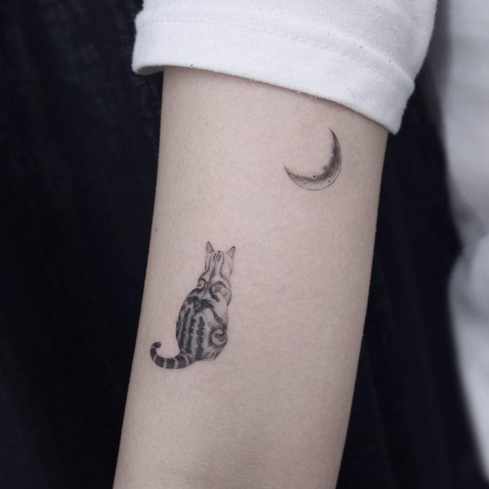 Kleines Tattoo am Oberarm, Katze und Halbmond, weißer Ärmel, Ideen für Mini Tattoos
