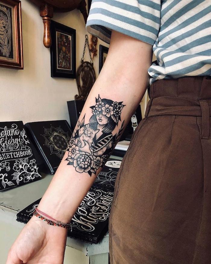 Schönes weibliches Tattoo am Unterarm, Mädchen mit Blumenkranz hält Katze, gestreiftes Shirt, braune Hose mit hoher Taille