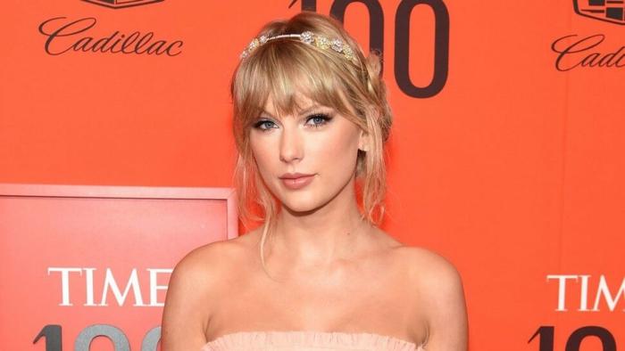 Taylor Swift mit einem rosa Kleid und Diamanten Schmuckstück auf einem roten Hintergrund