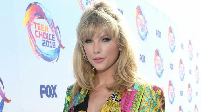 Taylor Swift mit einem bunten Kleid und mittellanges Haar, kleine Ohrringe, Album Lover