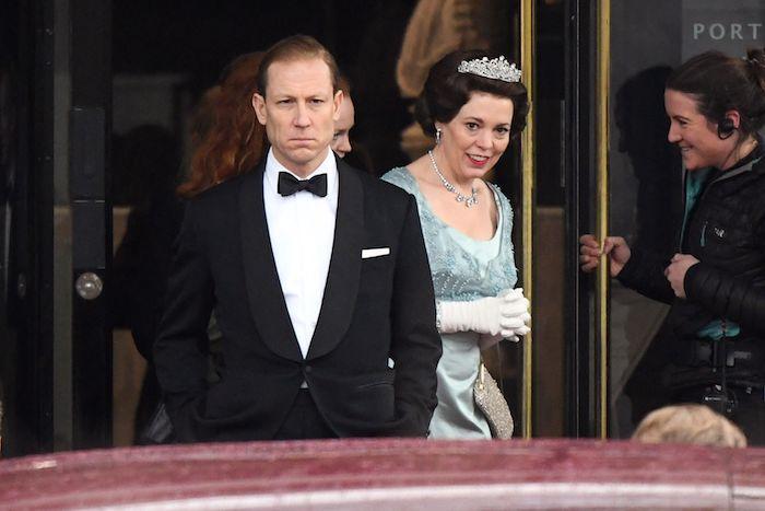 eine königin mit einer großen weißen krone und einer halskette und blauem kleid, mann mit kostüm, the crown von netflix