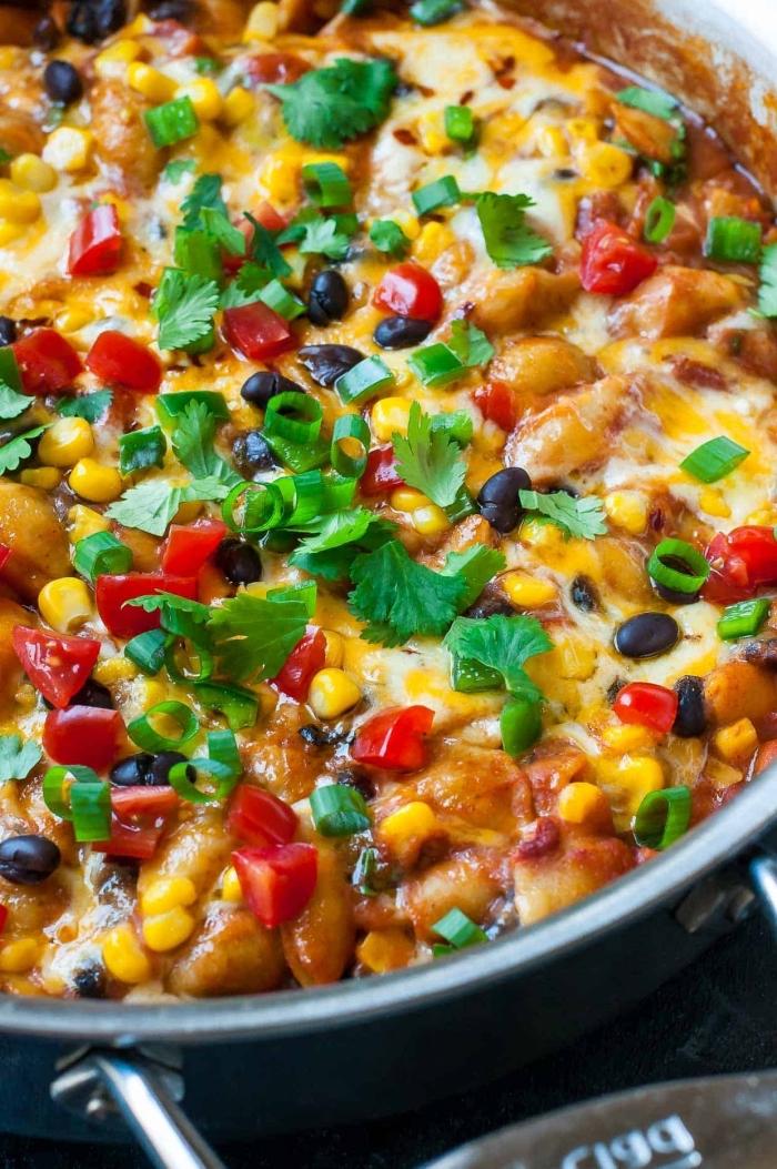 vegetarische gerichte für gästem kasserolle mit bohnen, käse, cherry tomaten und käutern, mittagessen