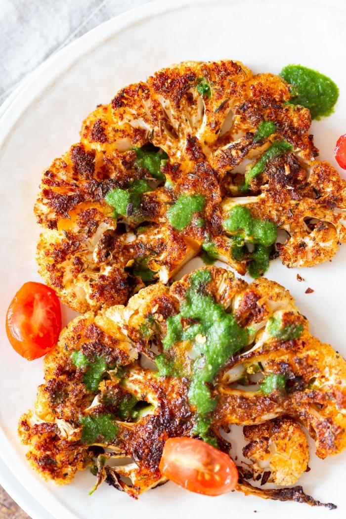 gebackenes blumenkohl mit gewürz garniert mit grüne soße und cherry tomaten, vegetarische gerichte schnell