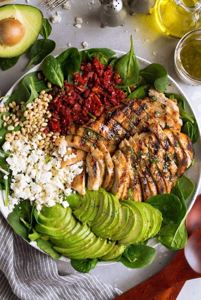 gesunde rezepte zum abnehmen, großer salat mti avocado, basilikum und spinat, käse, samen, trockene tomaten und hähnchenbrustfillet